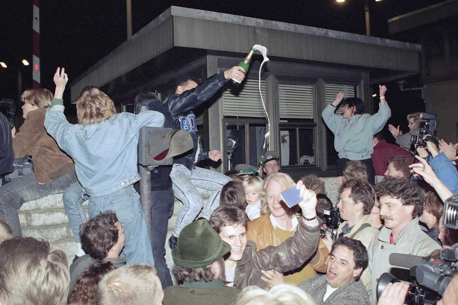 East and West Berliners mingle as they celebrate in front of a control station on East Berlin territory during the opening of the borders to the West following the announcement by the East German government that the border to the West would open. Photo taken in the early hours of November 10, 1989.